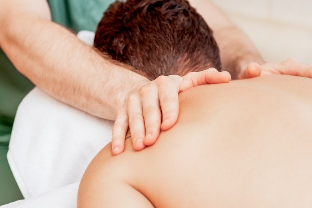 Young man receiving back massage in spa beauty salon.