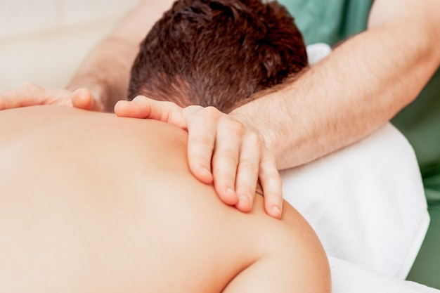 Молодой человек получает массаж спины.