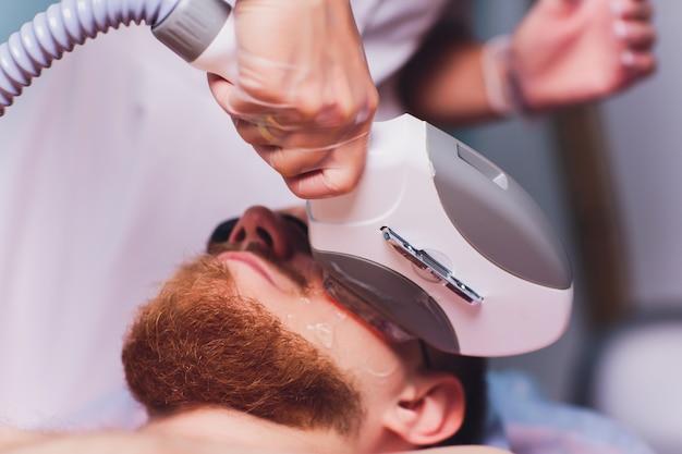 Молодой человек получает лазерное удаление волос лечение в центре красоты.