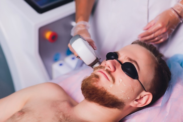 Young man receiving laser hair removal treatment at beauty center.