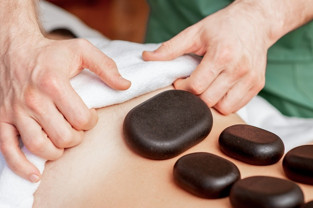 Young man receiving a stone massage on back while hands of massage therapist puts stones on her back.