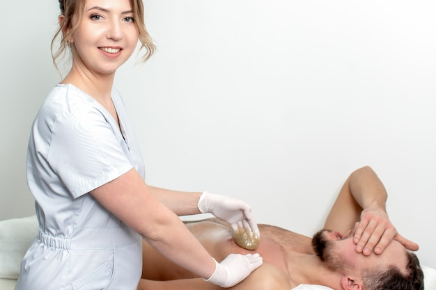 Young man receiving waxing chest by young female cosmetologist in beauty salon. portrait of young female cosmetologist during waxing male chest