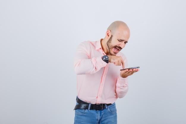 携帯電話で音声メッセージを録音する若い男