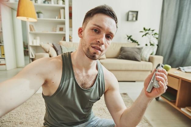 Молодой человек записывает себя, сидя на полу в центре гостиной и делая упражнения для рук и мышц рук