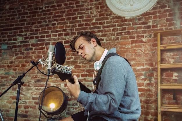 若い男が音楽を録音し、ギターを弾き、家で歌う
