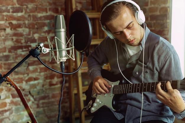 Молодой человек записывает музыку, играет на гитаре и поет дома
