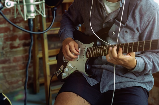 Young man recording music, playing guitar and singing at home