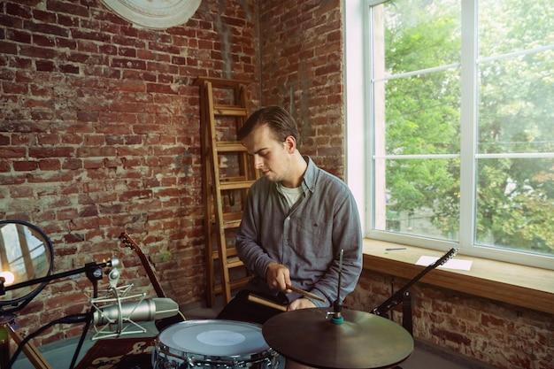 Молодой человек записывает музыкальное видео в блоге, домашний урок или песню, играет на барабанах или делает трансляцию в интернете, сидя на рабочем месте на чердаке или дома. понятие о хобби, музыке, искусстве и творчестве.