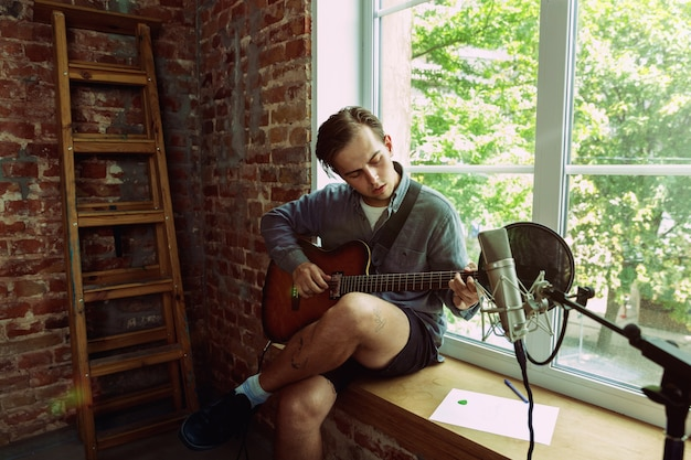 ロフトの職場や自宅に座って、ミュージックビデオのブログ、ホームレッスンや歌を録音したり、ギターを弾いたり、インターネットの放送チュートリアルを作成したりする若者。趣味、音楽、芸術、創造の概念。