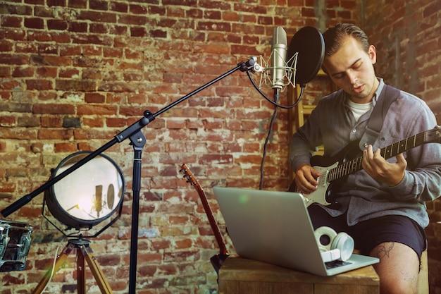ロフトの職場や自宅に座って、ミュージックビデオブログのホームレッスンを録音したり、ギターを弾いたり、インターネットの放送チュートリアルを作成したりする若者。趣味、音楽、芸術、創造の概念。