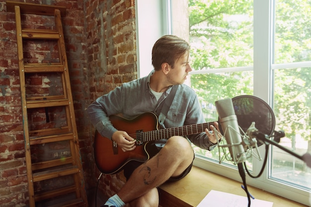 Young man recording music video blog, home lesson or song, playing guitar or making broadcast internet tutorial while sitting in loft workplace or at home