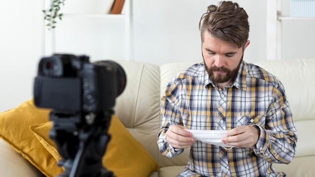 Молодой человек записывает видео дома с маской для лица
