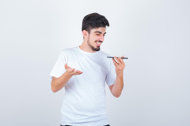 Tシャツで携帯電話に音声メッセージを録音し、幸せそうに見える若い男