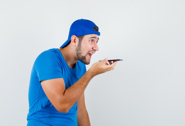 Young man recording voice message on phone in blue t-shirt and cap front view.