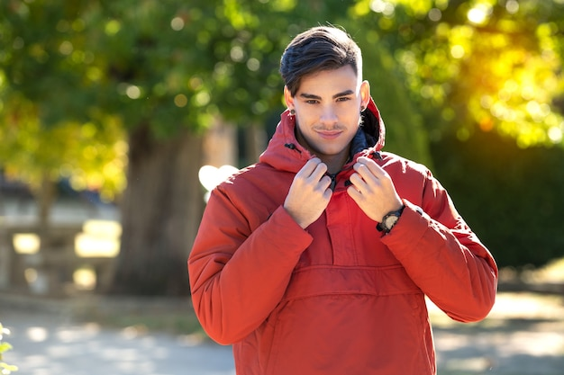 Young man in red coat buttoning his collar in the park on a cold sunny day.