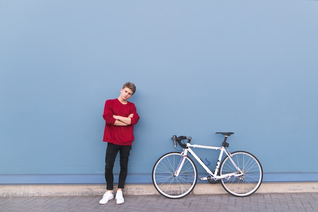 Young man in a red sweatshirt standing by a bicycle on a blue background