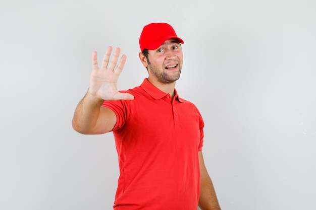 Young man in red t-shirt, cap showing refusal gesture politely