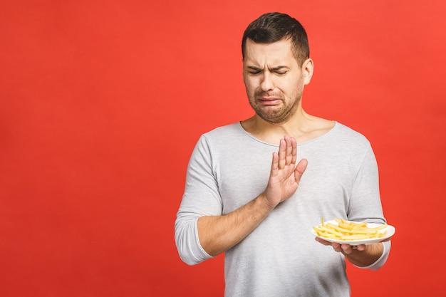 Молодой человек отвергает предложенную нездоровую пищу