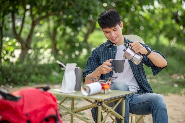 젊은 남자는 캠핑하는 동안 자연 공원에서 커피와 함께 휴식을 취합니다.