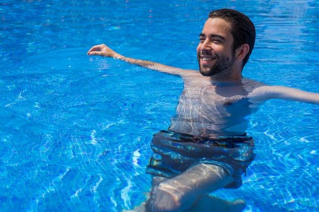 プールでリラックスした若い男