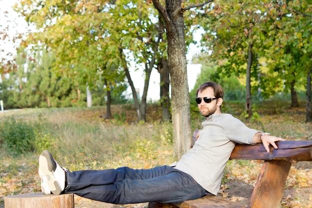 Молодой человек отдыхает на солнце, сидя на деревенской деревянной скамейке с поднятыми ногами на пне