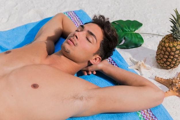 若い男がビーチでリラックス