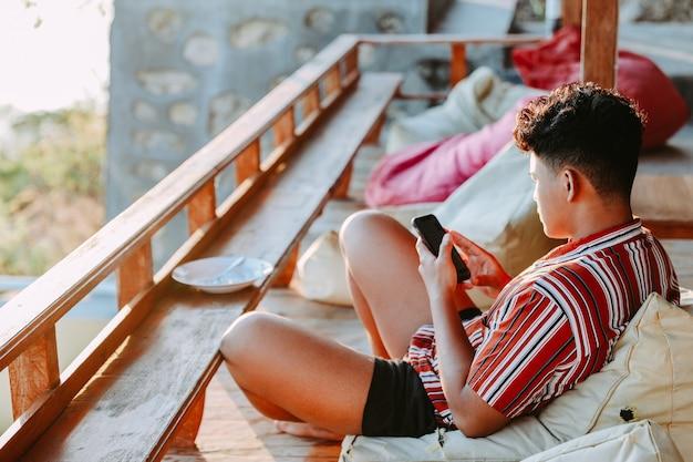젊은 남자가 발코니에서 빈백 위에서 휴식을 취하고 스마트폰을 하고 있다