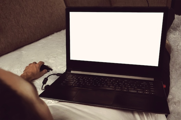 Young man relaxing on the sofa with a laptop. freelancer lefty works at a computer at home lying in bed. blank screen monitor for design layouts