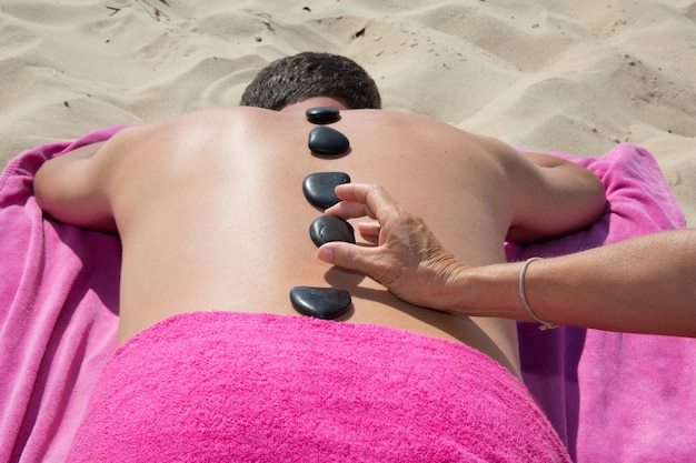 Young man relaxing with hot stones on back