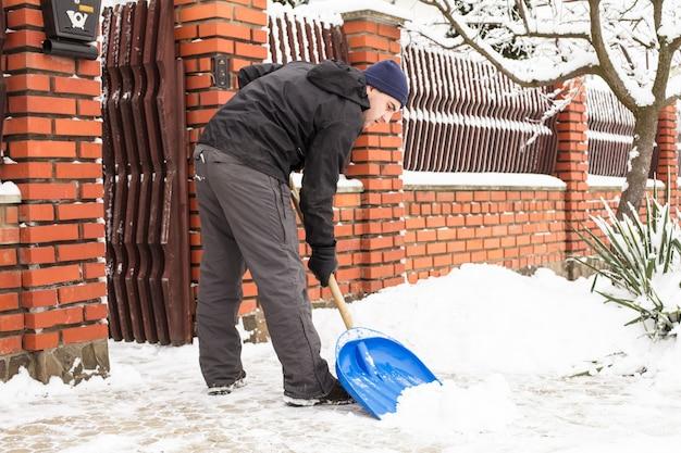 若い男が郊外の家の近くで除雪