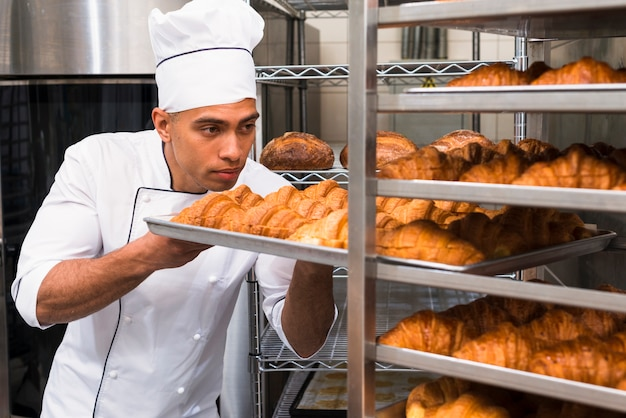 Young man removing the baking croissant tray from the shelf