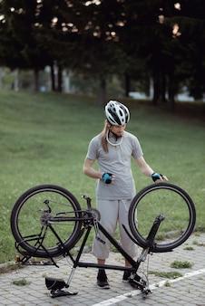 공원에서 자전거를 수리하는 젊은 남자