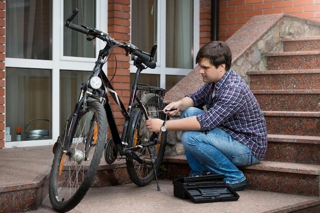 자전거 뒷바퀴를 수리하는 청년