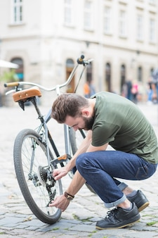 Young man repairing his bicycle on street in city