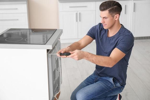 부엌에서 오븐을 수리하는 젊은 남자
