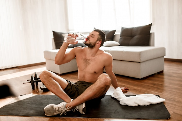 Young man resting and drinking water after working out