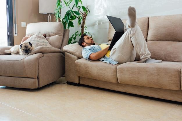 Молодой человек отдыхает на диване дома и использует ноутбук со своей собакой рядом с ним