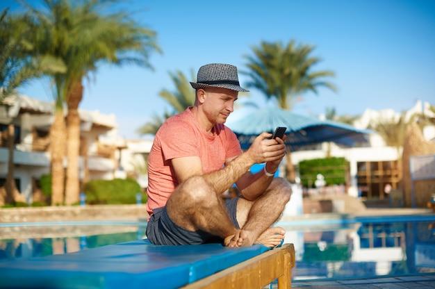 若い男がプールでサンラウンジャーで休んで、電話、フリーランスの仕事でsmsを入力
