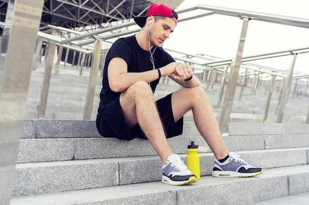 走った後、階段で休んでいる若い男。