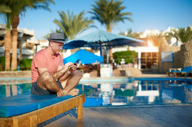 Young man resting on sun loungers by swimming pool and type sms on phone