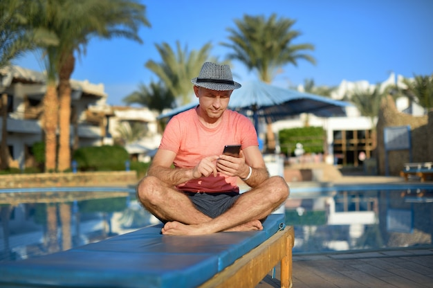 Young man resting on sun loungers by swimming relax in pool and type sms on phone, freelancer works remotely from the office mobile time