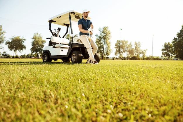 골프 카트에 기대어있는 동안 휴식하는 젊은 남자