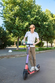 A young man rides an rented electric scooter in the park