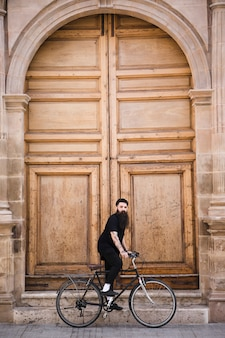 Young man riding the bicycle in front of large closed door