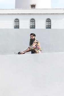 Young man riding the bicycle in front of wall