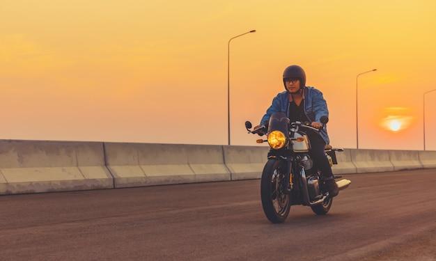日没時にアスファルト高速道路で大きなバイクのバイクに乗る若い男