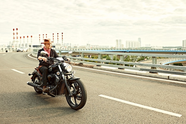 Young man riding big bike ,motorcycle on city road against urban and town building scene. motion blur
