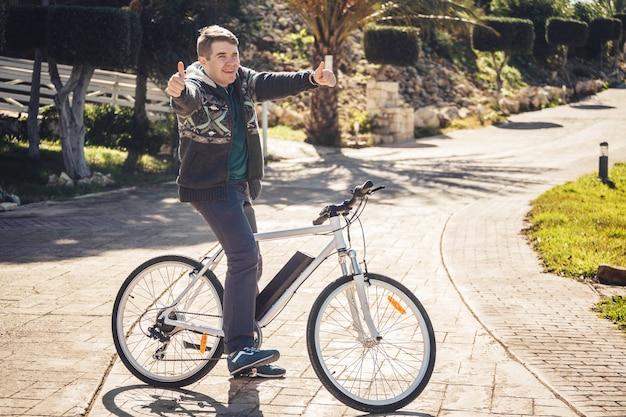 親指を立てて公園で自転車に乗っている若い男。