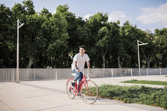 Young man riding bike in park