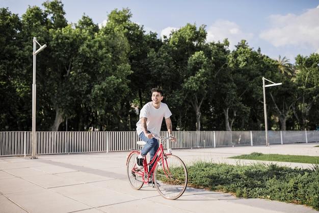 Молодой человек, езда на велосипеде в парке